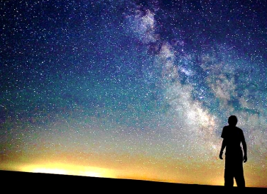 person-staring-and-looking-into-starry-sky